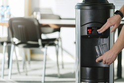 Water dispenser in the office, with hand filling a glass of water