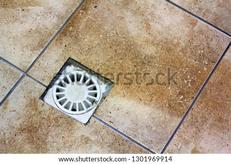 Water drain vent in kitchen, bathroom or basement ceramic tiled old vintage floor. Geometric abstract beige background. stock photo