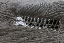Water drains from the drain hatch. Drainage fountain of sewage. Accident in the sewage system. Dirty sewage flows on the road. Drainage system for wastewater discharge does not work