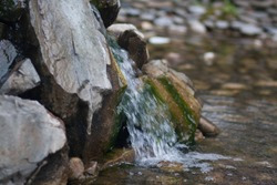 water drains from the stones in the stream stream. photo for your design. sheet horizontal orientation