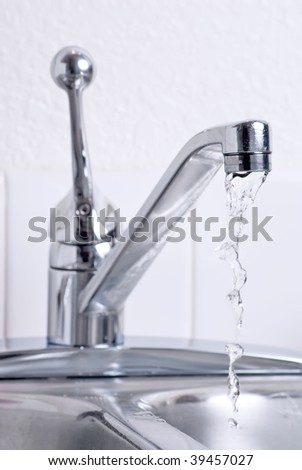 Water dribbling from a leaking faucet on the kitchen sink.