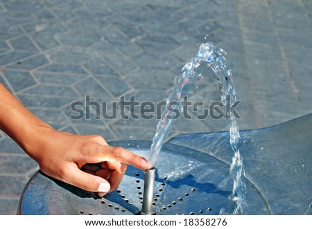 Water drinking fountain with human hand close up