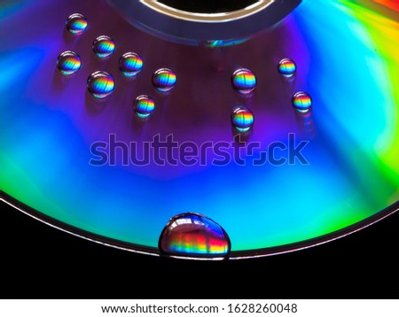 Water droplets dispersing or separating visible light on the surface of a compact disk. CD/DVD disk on a black background splitting light through droplets of water.