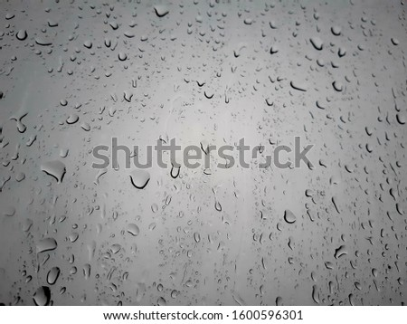 Water droplets from rain on the windshield of a vehicle.