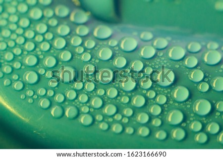 Water droplets on a blue and green  surface