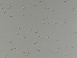 Water droplets on a gray glass panel (on the back of a mercury-coated glass).
