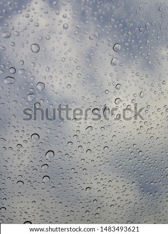 Water droplets on a pane of glass with a cloudy background.