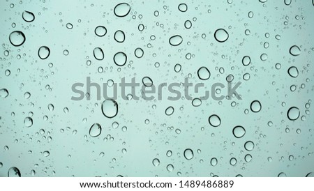 Water droplets on the glass on a blue background