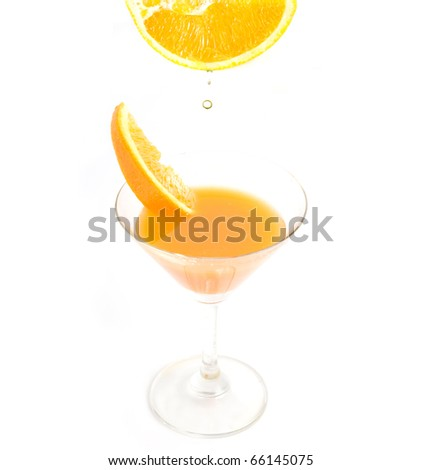 water dropping from fresh orange in to a glass of orange juice isolated on white