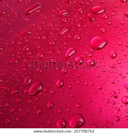 Water drops and droplets on a pink metallic paint car wet surface after the rain background