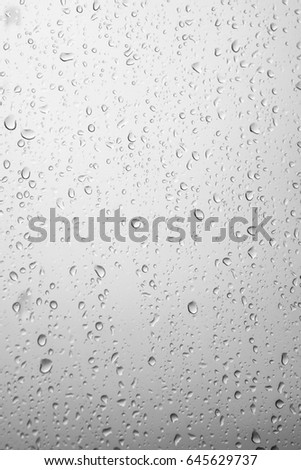 Water drops and rain drops on window glasses surface with cloudy background. Natural Pattern of raindrops on cloudy background. #645629737