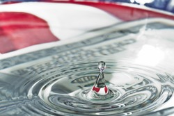 water drops and ripples with a one hundred dollar bill and an american flag as a background and reflection