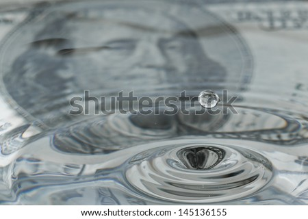water drops and ripples with a one hundred dollar bill as a background and reflection