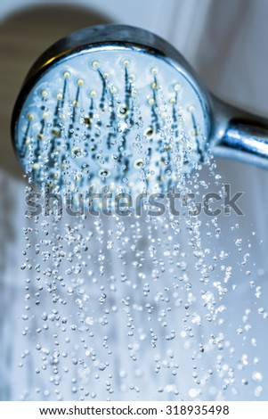 Water drops close-up dripping from the shower blue filtered