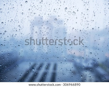 Water drops of rain on blue glass, view of city #306966890