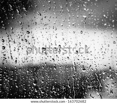 Water Drops Of Rain On Glass On Background Of Cloudy Sky