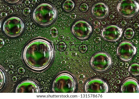 Water drops on a dark green glass close up