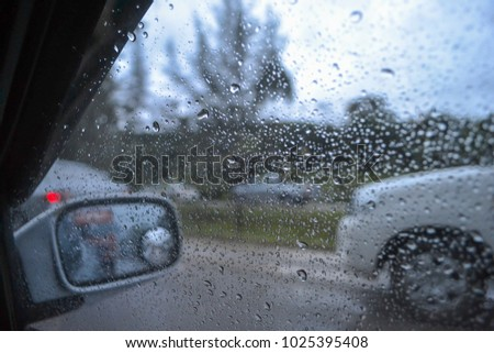 Water drops on car glass on the street. #1025395408