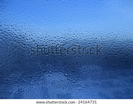 water drops on glass. blue background.