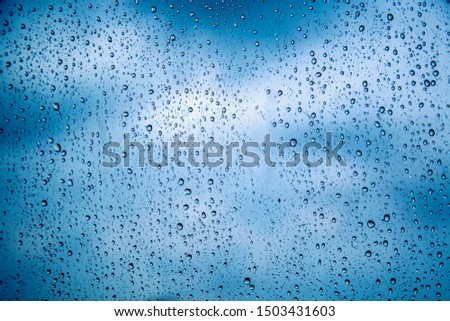 Water drops on glass with overcast sky from the storm. Rain drops on the glass with overcast sky in the rainy season. Can use for add text and abstract background.  #1503431603