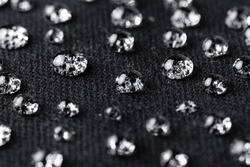 Water drops on waterproof black fabric close-up. Water resistant textile.