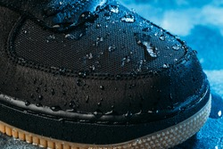 Water drops on waterproof membrane fabric of shoes surface, macro shot. New waterproofing technology for wear and footwear for active lifestyle