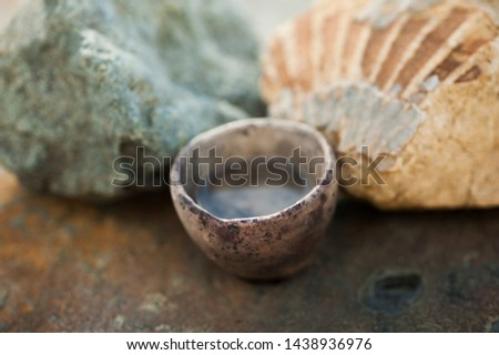 Water element still life photography study. A small primitive ceramic bowl holding pure water set on rock slab with a fossil seashell and green stone. The elemental healing purity of water nature. #1438936976