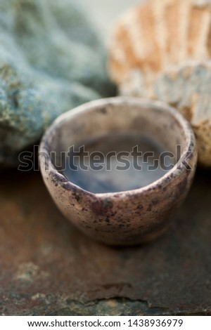 Water element still life photography study. A small primitive ceramic bowl holding pure water set on rock slab with a fossil seashell and green stone. The elemental healing purity of water nature. #1438936979
