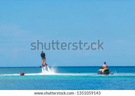 Water extreme sport. The guy is flying at the aquatic flyboard. Extreme rest on the sea. A lot of water pressure. Girl floating on a jet ski #1351059143