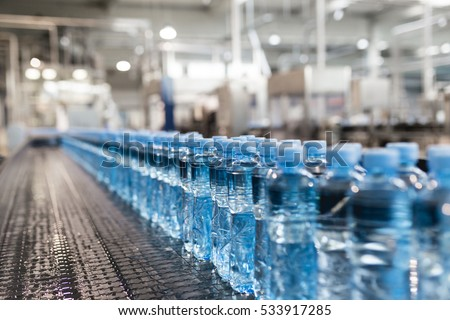 Water factory - Water bottling line for processing and bottling pure spring water into green glass small bottles. Selective focus. #533917285