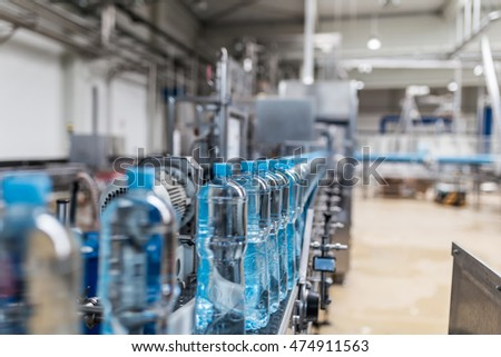 Water factory - Water bottling line for processing and bottling pure spring water into small bottles. Selective focus. #474911563