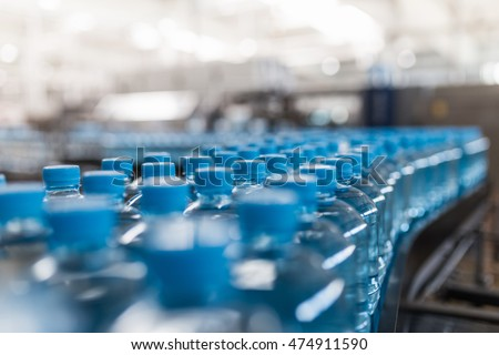 Water factory - Water bottling line for processing and bottling pure spring water into small bottles. Selective focus. #474911590