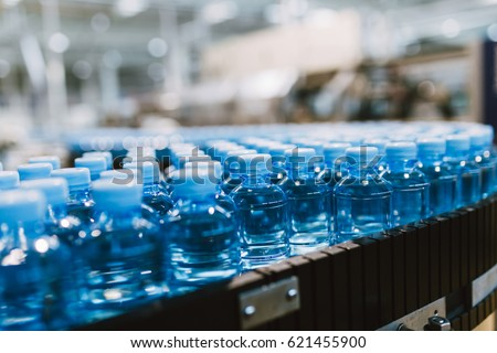 Water factory - Water bottling line for processing and bottling pure spring water into small blue bottles. Selective focus.  #621455900