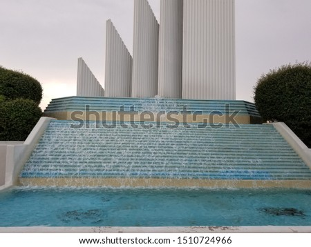 Water falling over aqua blue water fountain with pillar sculptures in background  #1510724966