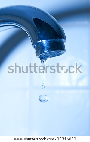 Water faucet on blue background