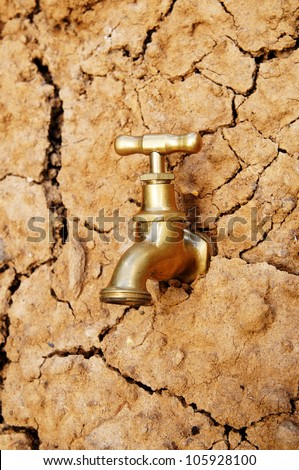 Water faucet on dry soil texture