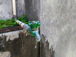 Water faucets and pipes are made of plastic. Detail of water faucet with water drip, looks old and vintage
