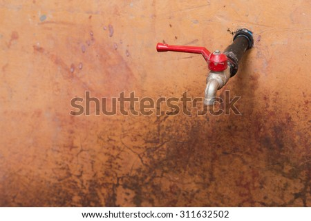 Water faucets on a old and vintage red concrete wall, with selective focus on the faucets.