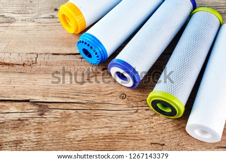 Water filters. Carbon cartridges on a wooden background. Household filtration system. #1267143379