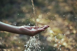Water flow to hand in the garden on nature background.