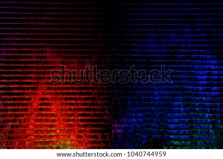 Water flowing down over backlit wall. Color fountain in modern style. Mysterious striped structure in shades of blue and red colors. Abstract background on the subject of nature or technology.