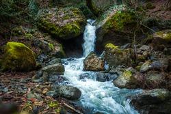 Water flowing down rocks, moss on the rocks, Svaneti, Georgia.