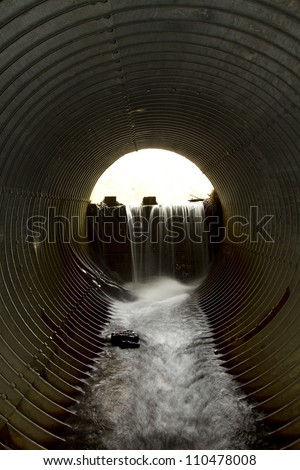 Water flowing from a dam theough a large pipe
