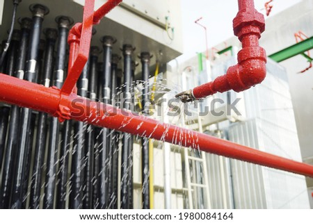 Water flowing from fire hose reel nozzles sprinkler system at Power transformer as part of the fire extinguishing system testing for safety in in part of an emergency in chemical plants.
