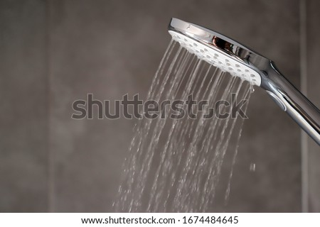 Water flowing from shower, close up. Modern bathroom interior. Chrome shower head with splashing water. Modern shower head. Shower in bathroom with water drops flowing.