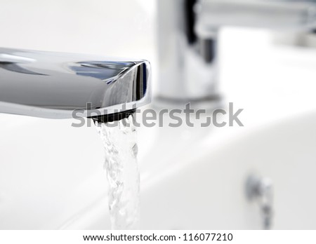 Water flowing from tap into basin
