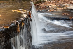Water flowing over a waterfall for a grist mill, with the autumn leaves floating in the water