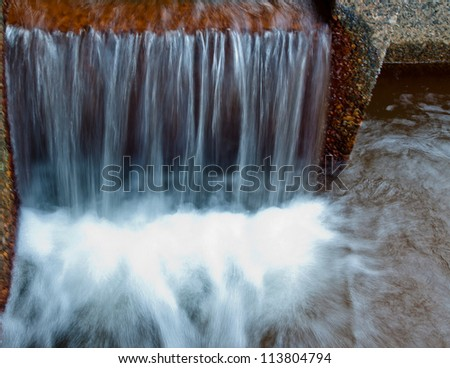 water flowing over edge of concrete wall into a pool of shallow water