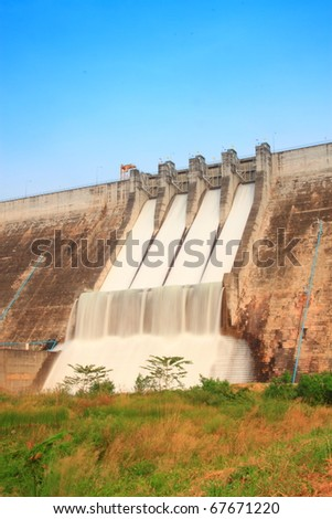 Water flowing over flood gates of a dam