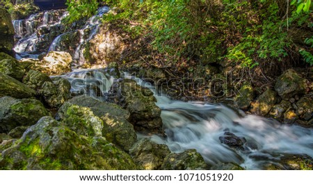 Water flowing over rocks in a natural green environment forming waterfalls. #1071051920